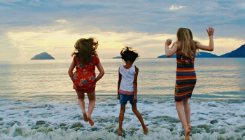 children_jumping_in_mid_air_by_sea